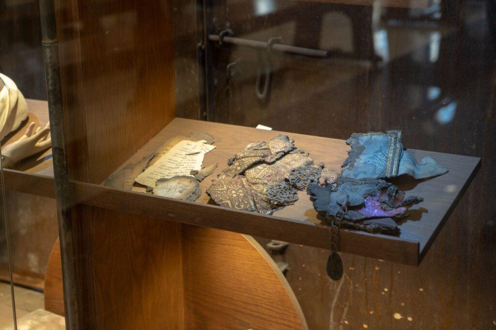 Fragments d'objets religieux brûlés dans une vitrine en mémoire des événements